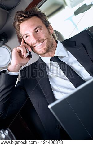 Businessman in full suit traveling in luxury limousine. Sitting in car working on laptop calling on phone. Business travel concept.