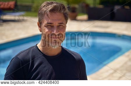 Portrait of mid adult man outdoor on vacation at poolside. Traveling, wellness resort, hotel garden, summer vacation. Happy older man in 50s, smiling.