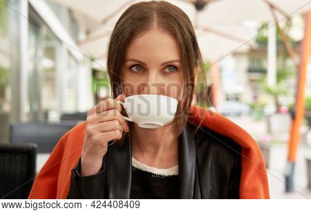 Young adult woman drinking tea on restaurant terrace.