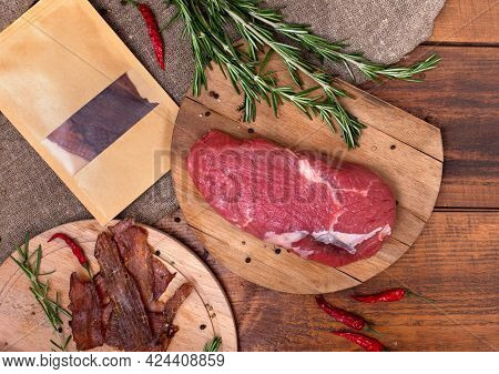 Jerky Meat, Raw Beef And Craft Paper Package On Circle Wooden Boards On Brown Background. Ingredient