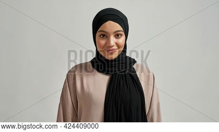 Portrait Of Cheerful Young Arabian Girl In Black Hijab Looking At Camera On Light Background, Widesc