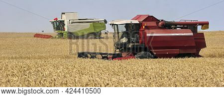 Harvester At Work. Wheat Field, Harvesting, Threshing. Combine Harvester And Header Close-up.