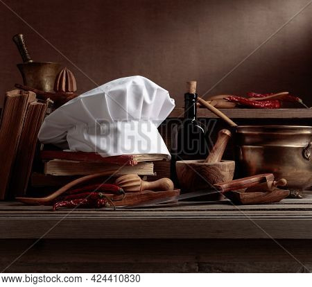 Chef's Hat, Vintage Cookbooks, And Old Kitchen Utensils On The Wooden Table. A Conceptual Image On T