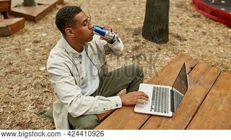 Top View Of Young African American Man With Energy Drink Working On Laptop Outdoors, Widescreen. Wor