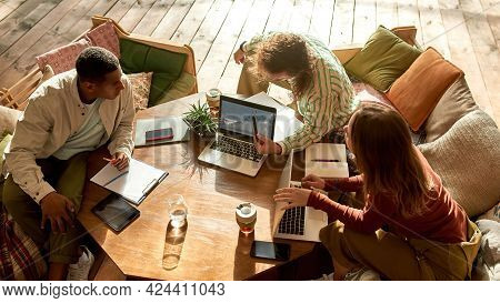 Cheerful Young Multiracial Colleagues Discussing Project On Laptop While Working Together In Large T