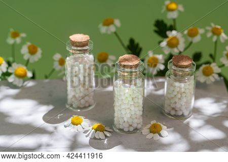 Classical Homeopathy Globules In Vintage Bottles On Background Of Fresh Chamomile Flowers. Alternati