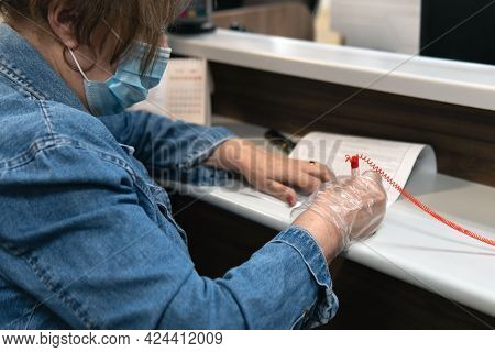 Senior Woman In A Medical Mask Sign Documents In The Russian Center Of State And Municipal Services
