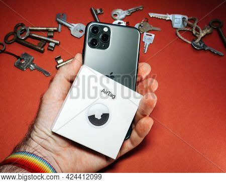 Paris, France - May 2, 2021: Man Pov Holding Package With Airtag And Iphone With Multiple Keys In Ba
