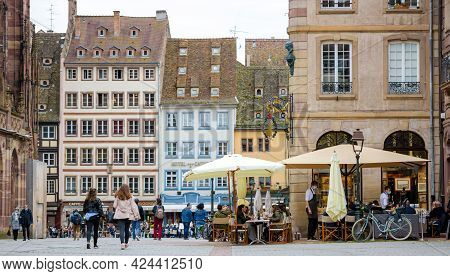 Strasbourg, France - May 19, 2021: People Locals And Toursits Walking Near Bars And Restaurants Terr