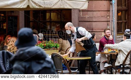 Strasbourg, France - May 20, 2021: Waiter With Protection Mask Cleaning The Table At The Outdoor Ter