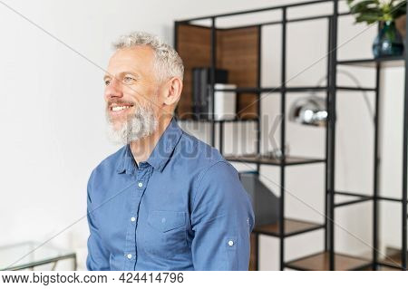 Serene Modern Middle Aged Businessman In Smart Casual Wear Leaned On The Desk Looks Away, Inspired A