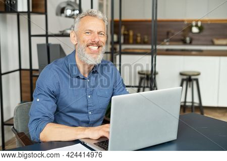 Portrait Of Mature Grey-haired Man Using Laptop In Home Office, Senior Male Entrepreneur Looks At Th