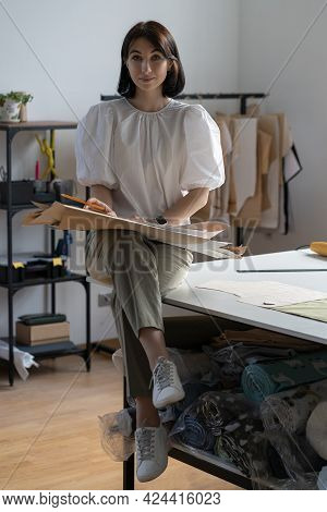 Young Girl Fashion Designer Wearing Trendy Handmade Outfit Sit On Table In Atelier Workshop. Dressma