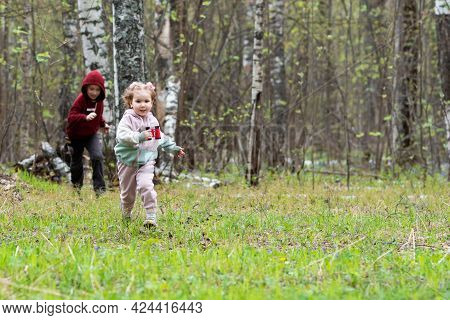 Brother And Sister Run A Race In A Clearing In The Forest