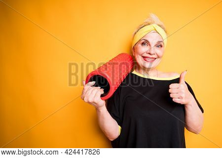 Cheerful Elderly Woman Holding Fascia In Hand And Raising Thumb Up While Standing On Yellow Backgrou
