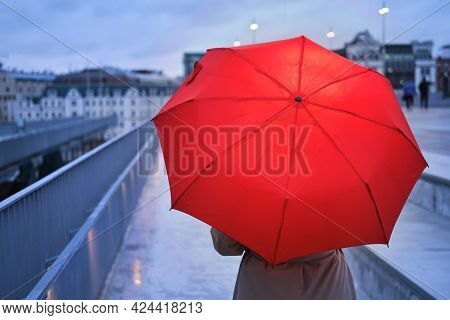 A Woman With An Umbrella In The Rain On The Background Of City Buildings
