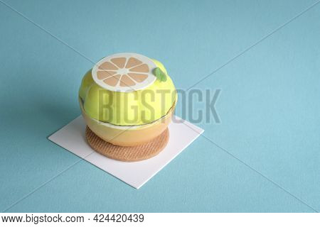 Gatou Cake In The Form And Shape Of Cut Lemon With Wafer Base. On Blue Background, Copy Space.