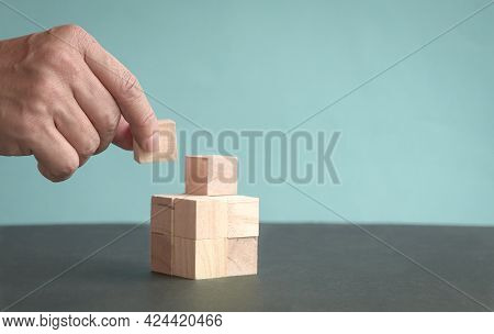 Hand To Put A Piece Of Wood Block To Establish A Wooden Cube. Copy Space.