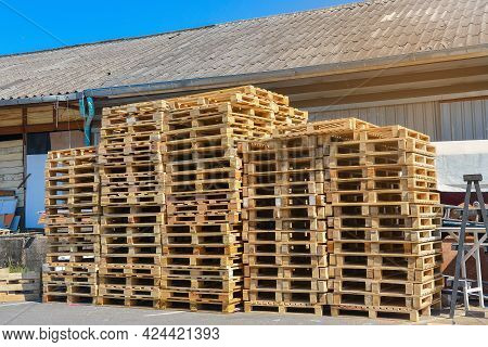 A Stack Of Pallets Sit Outside A Building, Wooden Pallet.