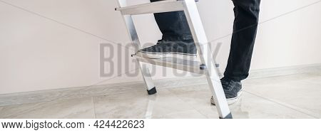 A Close Up Workers Feet On The Ladder Climb To The Top Against The Wall With Copy Space