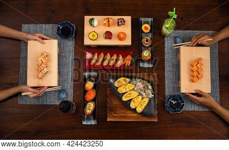 Elevated view of couple enjoying Japanese cuisine various side dishes by chopstick. Philadelphia, Tuna uramaki, Flower sush set, Gyoza,