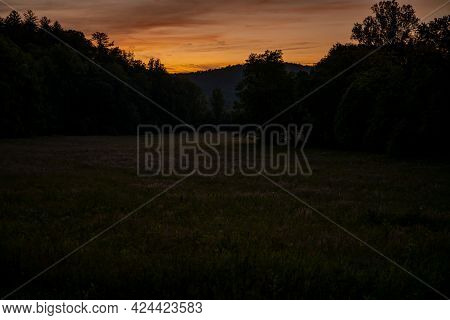 Fireflies Dot A Field At Sunset In Cades Cove In The Smokies