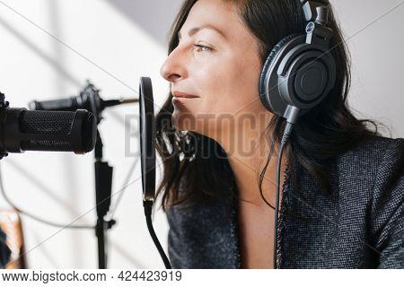 Female radio host broadcasting live in a studio
