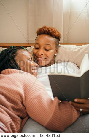 Happy lesbian couple cuddling and reading a book together