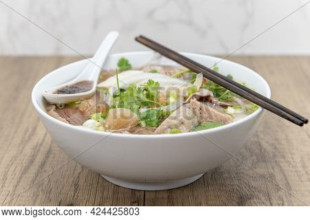 Hearty Bowl Of Pho Loaded With Meat, Broth, And Special Taro Sauce For A Complete Meal.