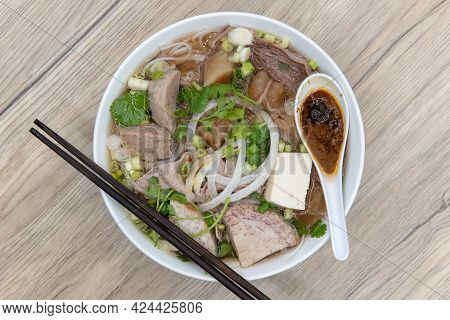 Overhead View Of Hearty Bowl Of Pho Loaded With Meat, Broth, And Special Taro Sauce For A Complete M