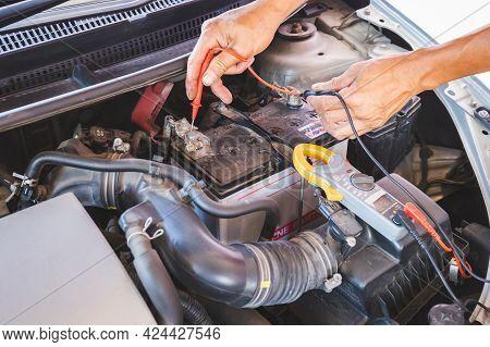 Auto Mechanic Working On Car Engine Checking Battery In Mechanics Garage, Repair And Maintenance Ser
