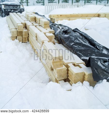 Timber Balks Partly Covered With Plastic Cover And Abandoned Outdoor Due To Blizzard