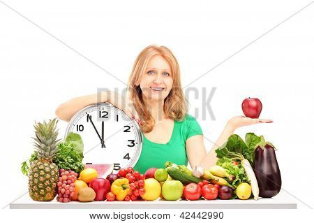 Woman with red apple, clock and fruit and vegetables on a table isolated on white background