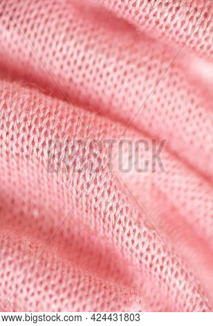 Large Folds Of Knitted Pink Fabric Close-up. The Structure Of The Weave Is Clearly Visible, Part Of