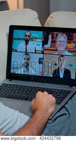 Over Shoulder View Of Man In Pajamas Having Online Conversation With Teammates Working At Online Tec