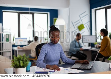 Dark Skinned Woman In New Business Office Looking At Charts Sitting At Desk, Company Manager. Divers