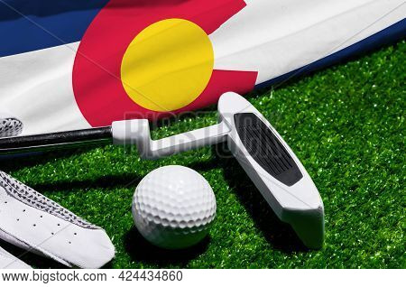 Golf Ball And Club With Flag Of Colorado On Green Grass. Golf Championship In Colorado