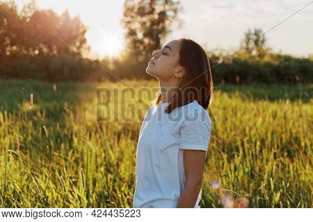 Profile Portrait Of Brunette Female Wearing White Casual Style Attire Posing In Green Field On Sunse