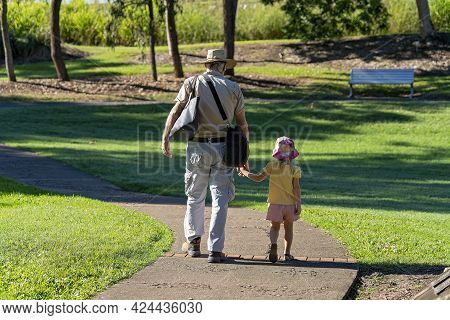 Mackay, Queensland, Australia - June 2021: A Grandfather Carrying Bags Holds His Granddaughter's Han