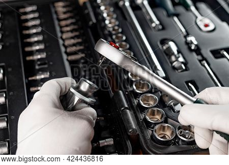 Hands Of Repairman In Gloves Close Up With Metal Steel Socket Ratchet Handle Over Toolbox, Pov.