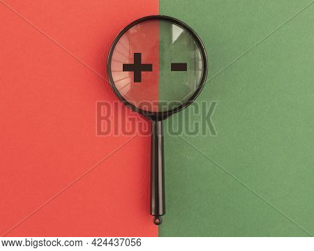 Plus And Minus Signs Through Magnifier On Red And Green Background. Concept Of Positive And Negative