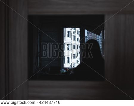 The Reflection Of The Woman In The Window With The View On The Other Apartments In The Suburb Of The