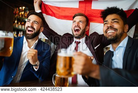 Group Of Friends At The Pub Watcing Football Game And Drinking Beer