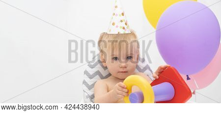 Adorable Caucasian Blonde Baby Girl, Sitting At High Chair By Colorful Balloons Wearing Birthday Hat