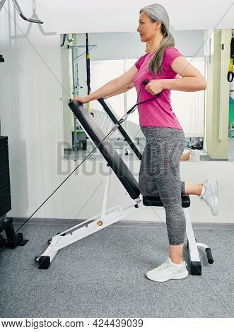 Mature Woman Working Out In Rehab Gym During Rehabilitation After Injury