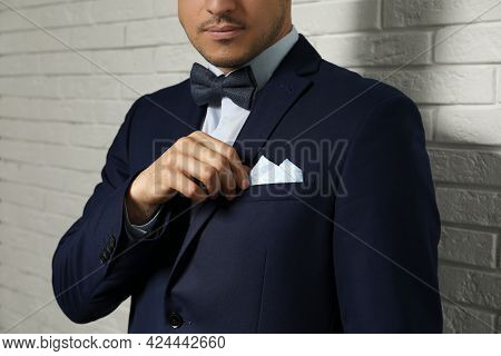 Man Fixing Handkerchief In Breast Pocket Of His Suit Near White Brick Wall, Closeup
