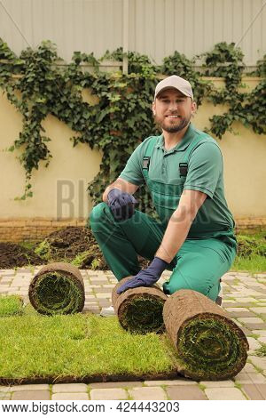 Worker Unrolling Grass Sods On Pavement At Backyard
