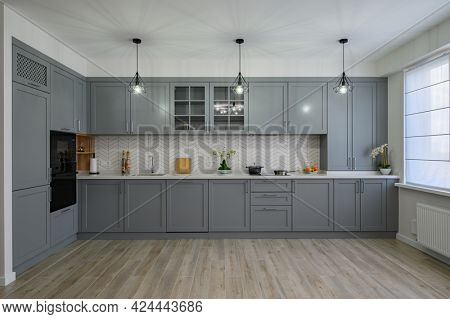 Trendy grey and white modern kitchen furniture showcase, front view