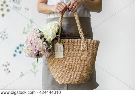 Woman carrying hydrangeas in a wicker bag