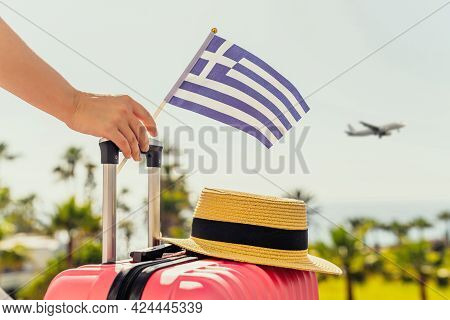 Woman With Pink Suitcase, Hat And Greece Flag Standing On Passengers Ladder And Getting Out Of Airpl